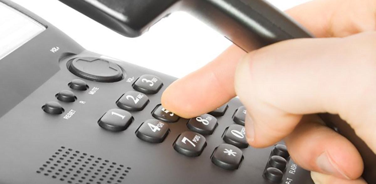 finger and keypad. dialing on black telephone.